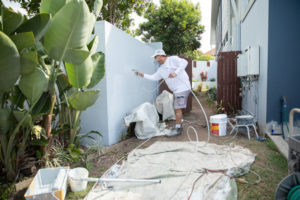 brisbane painter spraying paint on exterior wall